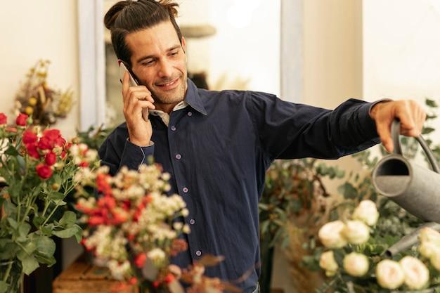 Ogrodnik rozmawia przez telefon i podlewa rośliny