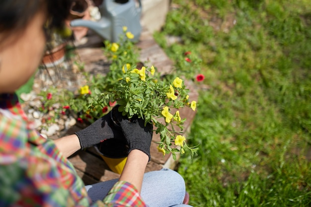 Ogrodnik sadzenia za pomocą narzędzi do doniczek. kobieta strony sadzenia kwiatów petunii w letnim ogrodzie w domu, na zewnątrz. pojęcie ogrodnictwa i kwiatów.