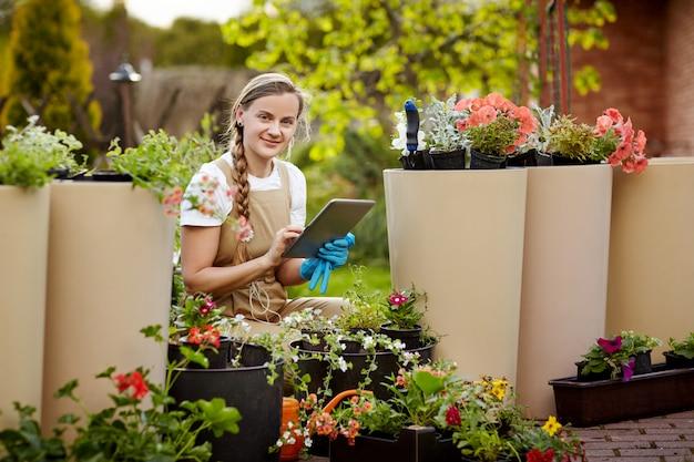 Ogrodnik sprawdza stan i dostępność kwiatów, sprawdza wpisy na tablecie.