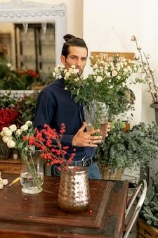 Ogrodnik trzyma duży wazon z liśćmi i kwiatami