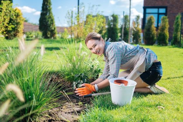 Ogrodnik w krótkich spodenkach. blond włosa uśmiechnięta ogrodniczka w krótkich dżinsowych szortach i białych tenisówkach sadząca nowe kwiaty