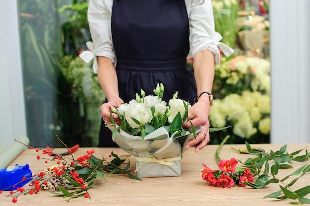 Ogrodnik w kwiaciarni robi bukiet. kwiaciarnia lifestyle. piękna kompozycja kwiatowa. szczegół.