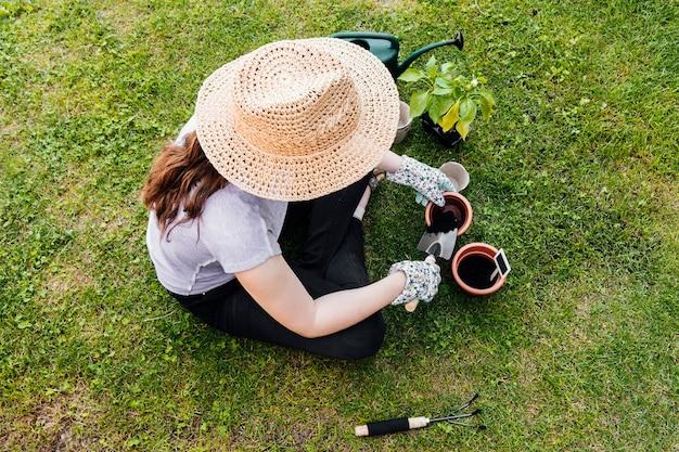 Ogrodnik wysokiego kąta siedzi i sadzi