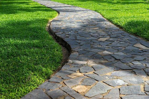 Ogrodowa droga kamienna falująca wśród zielonego trawnika. projektowanie krajobrazu parku miejskiego.