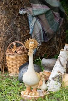 Ogrodowa figurka gęsi w słomkowym kapeluszu na tle stogów siana i żeliwnych doniczek