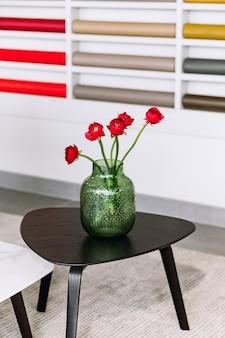 Ogrodowe czerwone róże w szklanym wazonie na stole