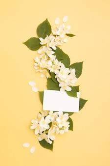 Ogrodowe kwiaty jaśminu z liśćmi i pustą wizytówką na żółtym tle