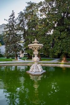 Ogrody pałacu dolmabahce z dużą ilością zieleni, fontanną i stawem z wodą, turcja