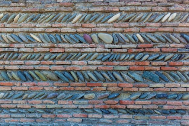Ogrodzenia i ściany domów są w wioskach i miastach gruzji wykonane z różnych kamieni, tła z kamienia naturalnego, tekstury kamienia.