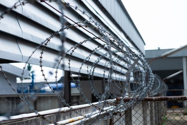 Ogrodzenia z drutu kolczastego zainstalowane na ścianie w celu ochrony obszaru przed złodziejami lub zapobiegania ucieczce więźniów.