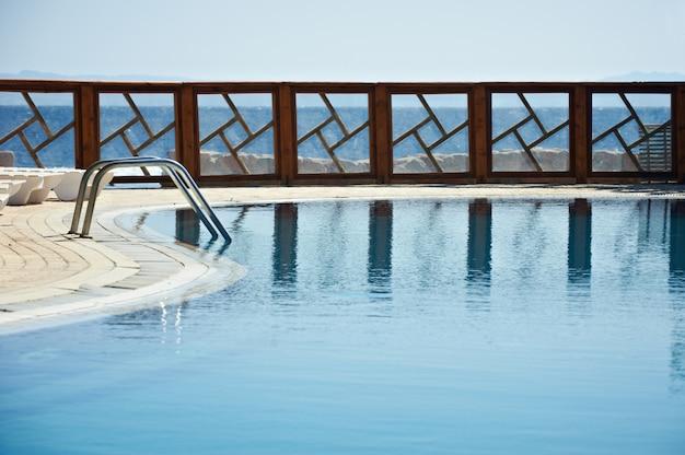 Ogrodzenie basenu ośrodka odbite na wodzie.