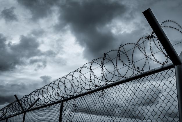 Ogrodzenie bezpieczeństwa więzienia. ogrodzenie z drutu kolczastego. granica bariery. granica ściany bezpieczeństwa. teren prywatny. koncepcja strefy wojskowej.