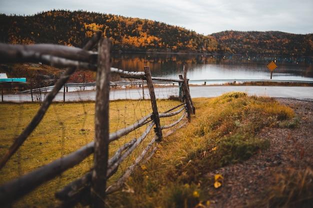 Ogrodzenie drewniane otaczające pole w pobliżu jeziora w ciągu dnia