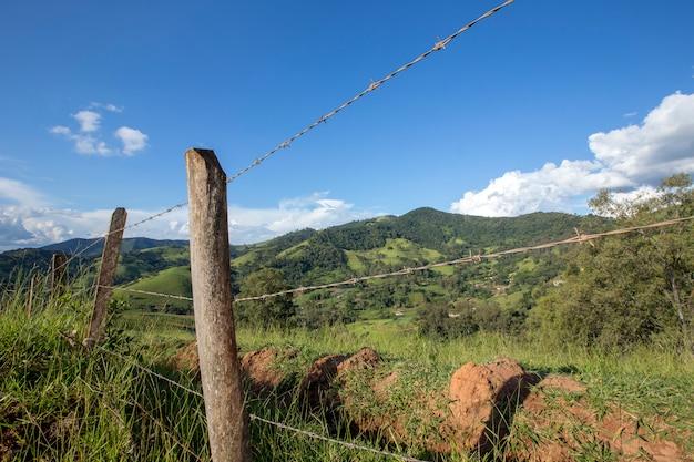 Ogrodzenie i drzewo na pierwszym planie z niebieskim niebem i wzgórzem w tle. wieś brazylii