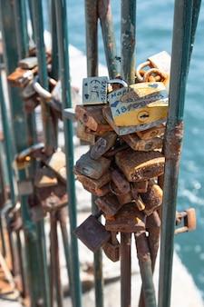 Ogrodzenie od strony morza z wieloma małymi zardzewiałymi zamkami z osobistymi napisami