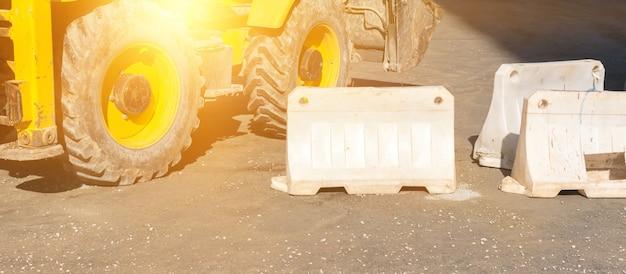 Ogrodzenie placu budowy i ciężkie koła koparki. zdjęcie tła transparentu robót drogowych