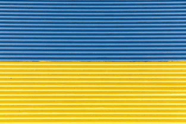 Ogrodzenie pomalowane na niebiesko-żółtą flagę ukrainy