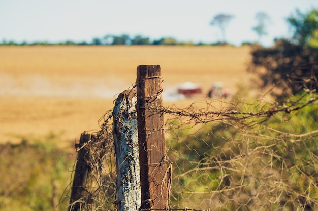 Ogrodzenie starego drewna na farmie z ciągnikiem