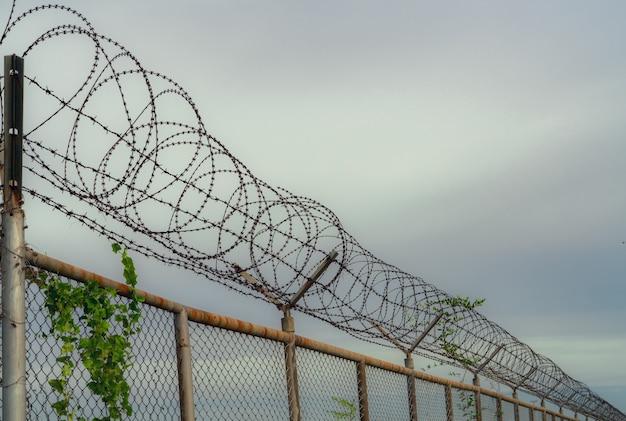 Ogrodzenie więzienne. ogrodzenie z drutu kolczastego. ogrodzenie więzienia z drutu brzytwy. granica bariery. ścianka bezpieczeństwa granicznego. więzienie za aresztowanie przestępców lub terrorystów. teren prywatny. koncepcja strefy wojskowej.