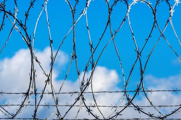 Ogrodzenie z drutem kolczastym przeciw niebieskiemu niebu z chmurami