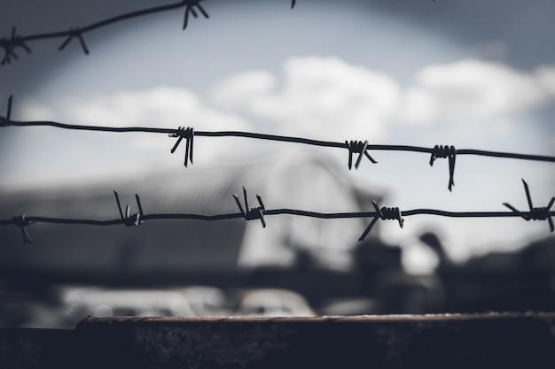 Ogrodzenie z drutu kolczastego na tle dramatycznego, ciemnego nieba.