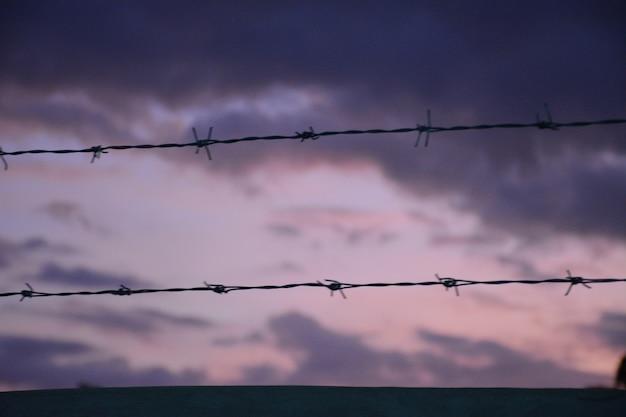 Ogrodzenie z drutu kolczastego z twilight sky, aby czuć się cicho, samotnie i pragnąć wolności