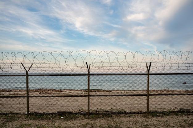 Ogrodzenie z siatki z drutu kolczastego na brzegu morza wieczorem. pojęcie wolności