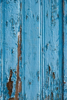 Ogrodzenie ze starych niebieskich desek z popękaną starą farbą ułożone pionowo