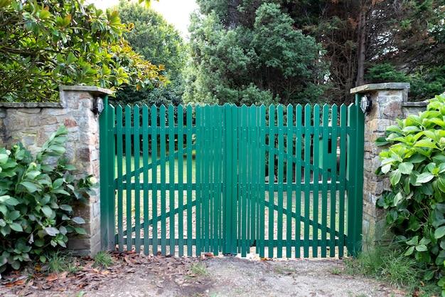 Ogrodzenie zielone z drewnianych desek pionowych.