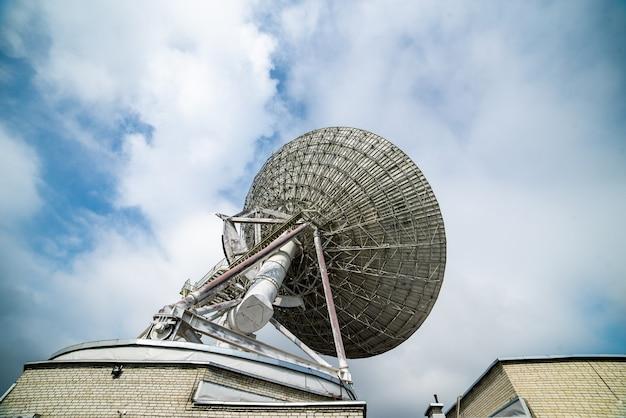 Ogromna antena satelitarna do komunikacji i odbioru sygnału z planety ziemia. obserwatorium poszukujące sygnału radiowego w kosmosie o zachodzie słońca.