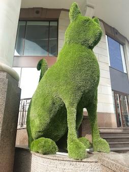 Ogromna figura dekoracyjna o profilu kota wykonana z zielonego miękkiego materiału w pobliżu sklepu