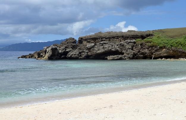 Ogromna formacja skalna w pobliżu morza pod zachmurzonym niebem