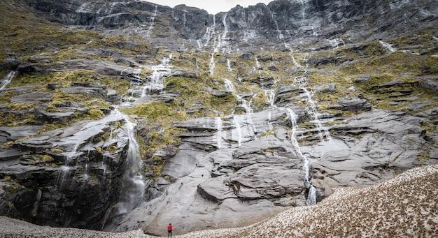 Ogromna ściana wodospadów z osobą znajdującą się na dole fiordland nowa zelandia