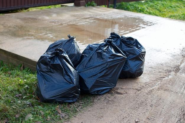 Ogromne czarne plastikowe torby ze śmieciami stojące w pobliżu domu. koncepcja selektywnej zbiórki i utylizacji odpadów do recyklingu