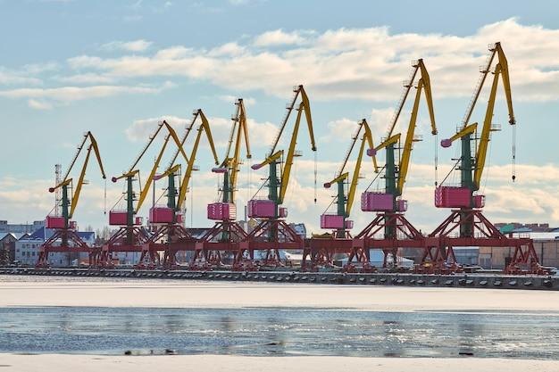 Ogromne dźwigi portowe w porcie morskim. dźwigi portowe do ciężkich ładunków w porcie, stoczni kontenerowej, terminalu kontenerowym. biznes i handel, logistyka. zimowa scena przemysłowa.
