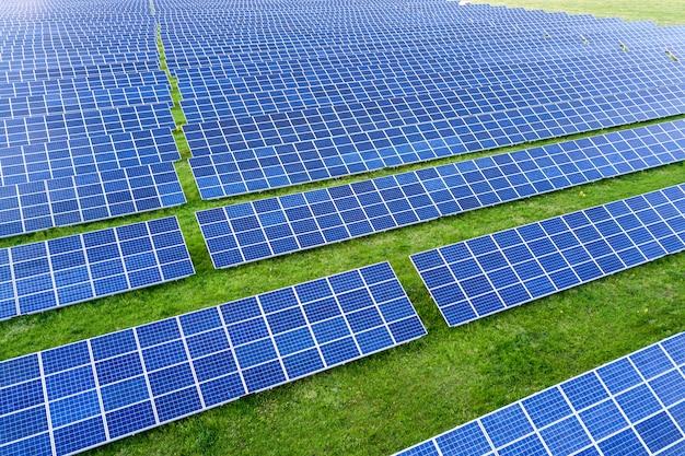 Ogromne pole systemu fotowoltaicznych paneli słonecznych wytwarzających odnawialną czystą energię na tle zielonej trawy.
