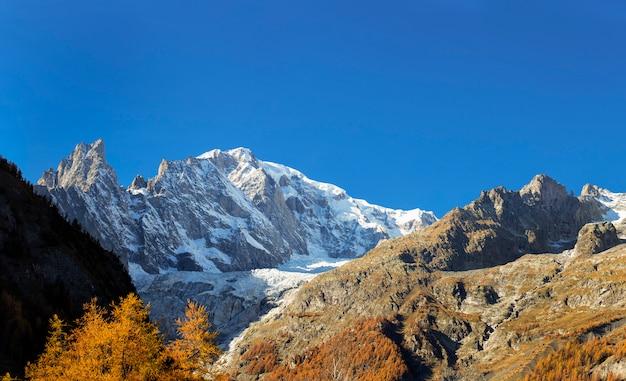 Ogromne śnieżne góry jesienią z kolorowymi drzewami