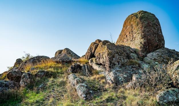 Ogromne złoża starych minerałów kamiennych pokryte roślinnością na łące wypełnionej ciepłym słońcem ukrainy i jej piękną przyrodą