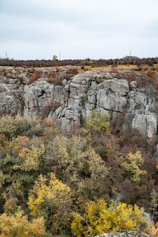 Ogromne złoża starych minerałów kamiennych pokryte roślinnością na łące wypełnionej ciepłym słońcem