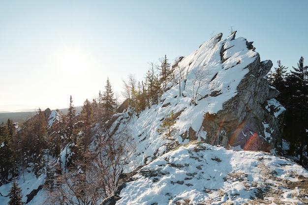 Ogromny kamień pokryty śniegiem na szczycie skalistej góry otoczony drzewami lasu mieszanego na tle błękitnego nieba ze słońcem w zimowy dzień