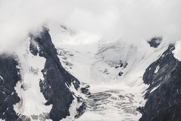Ogromny lodowiec na dużej górze w niskich chmurach.