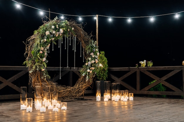 Ogromny ozdobny krąg wykonany z wierzby, zieleni i jasnopomarańczowych róż z płonącymi świecami