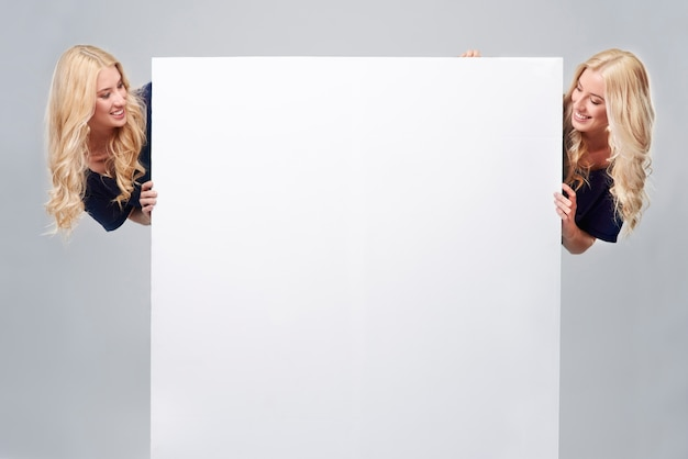 Ogromny pusty plakat i dwie siostry