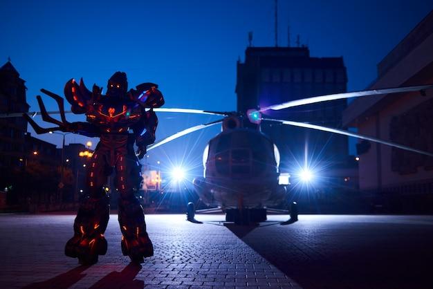 Ogromny robot-transformator stojący przed sylwetką helikoptera wojskowego.