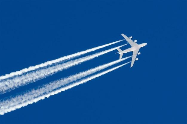 Ogromny samolot duże cztery silniki lotnicze lotnisko chmury smugowe.