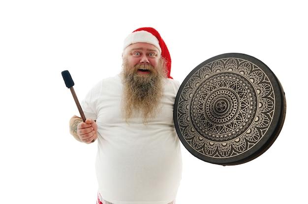 Ogromny szaman mężczyzna z wytatuowanymi ramionami w czapce świętego mikołaja pozujący z szamańskim tamburynem wyrażającym szczęście i radość.