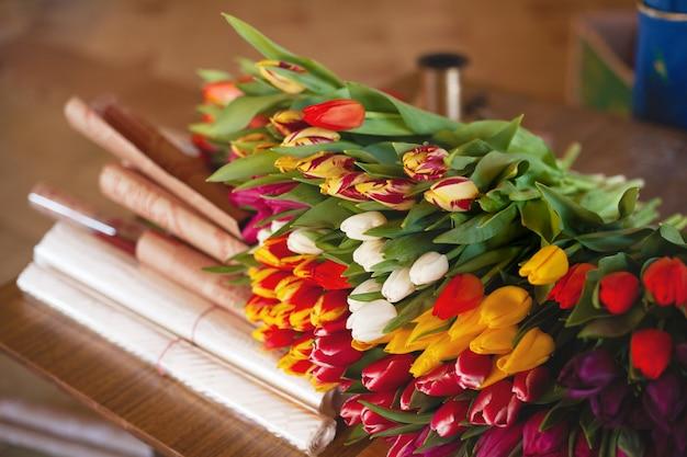 Ogromny wielobarwny bukiet tulipanów leży na stole w kwiaciarni
