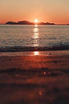 Ogromny zachód słońca nad wyspami odbijający się nad oceanem ze słońcem i pływami na plaży nad piaskiem wiosną, w kolorowych odcieniach z przestrzenią do kopiowania
