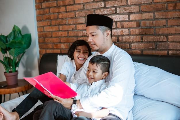 Ojca azjata czyta książkę dla jego dwojga dzieci