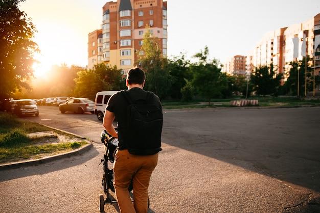 Ojca tata z nowonarodzonym pram spacerowiczem outside podczas lato wieczór zmierzchu